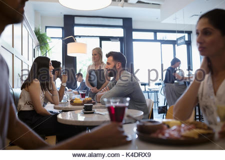 Customers eating and drinking wine at cafe tables - Stock Photo