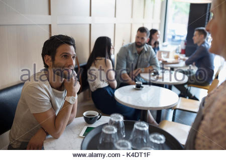 Male customer talking to waitress in cafe - Stock Photo