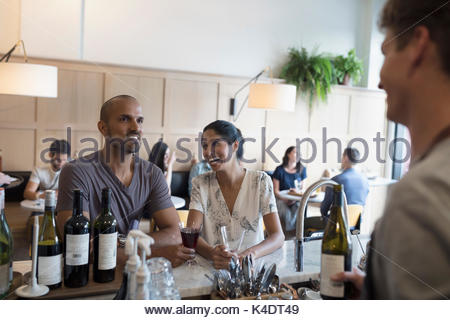 Wine steward talking with couple customers drinking wine at cafe counter - Stock Photo