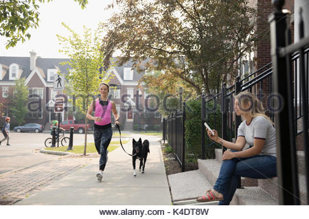 Female runner running with dog and woman texting with cell phone on neighborhood sidewalk - Stock Photo