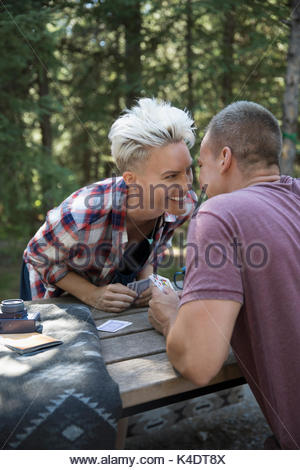 Affectionate couple kissing, playing cards at campsite picnic table - Stock Photo