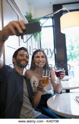 Happy couple taking selfie, drinking wine and beer at cafe table - Stock Photo
