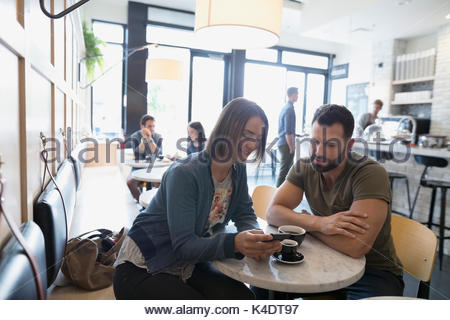 Couple drinking coffee and using cell phone in cafe - Stock Photo