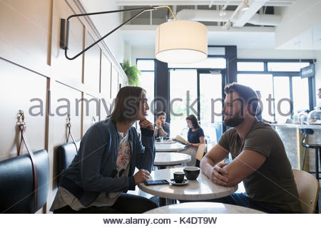 Couple drinking coffee and talking in cafe - Stock Photo