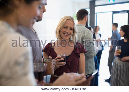Friends talking and drinking wine, using digital tablet and socializing in bar - Stock Photo