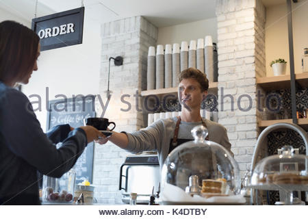 Male barista serving coffee to female customer in cafe - Stock Photo