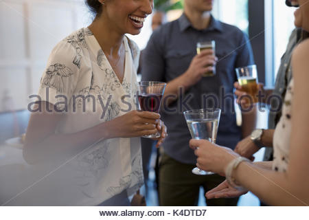 Friends talking and drinking wine, socializing in bar - Stock Photo