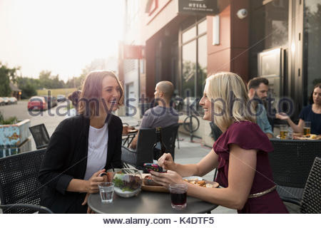 Smiling women friends drinking wine at sidewalk cafe - Stock Photo