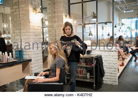 Female hair stylist blow drying hair of customer in hair salon - Stock Photo