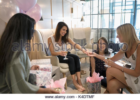 Bride-to-be showing wedding ring to bridesmaid friends celebrating bridal shower in nail salon - Stock Photo