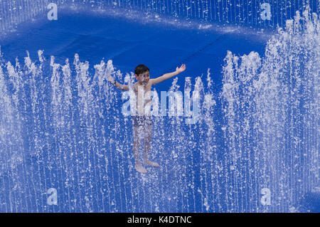 Happy boy playing outside in the Southbank Centre Appearing Rooms water fountain with its blue background - Stock Photo