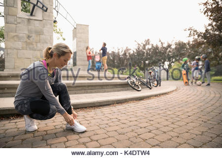 Female runner tying shoes in park - Stock Photo