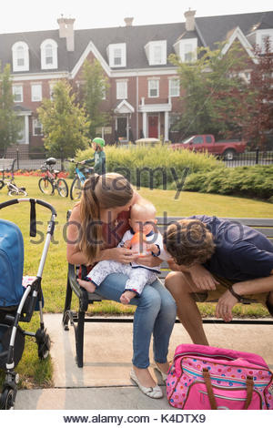 Young family with baby sitting on neighborhood park bench - Stock Photo