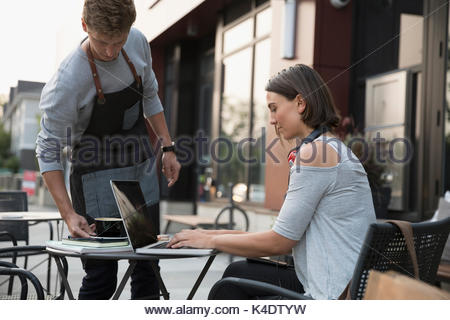 Waiter serving coffee to woman using laptop at sidewalk cafe - Stock Photo