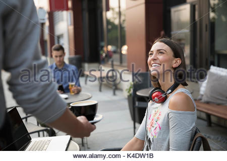 Waiter serving coffee to smiling woman using laptop at sidewalk cafe - Stock Photo
