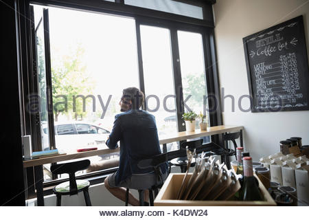 Pensive man sitting at window in cafe - Stock Photo