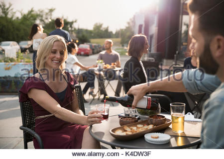 Man pouring red wine for girlfriend at sidewalk cafe - Stock Photo