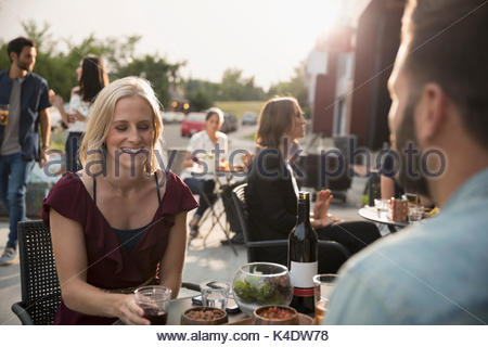 Smiling woman drinking wine with boyfriend at sidewalk cafe - Stock Photo