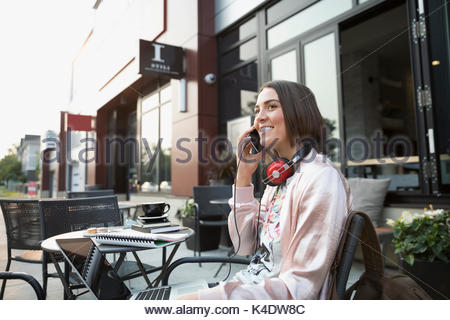 Smiling brunette woman with headphones talking on cell phone at laptop at sidewalk cafe - Stock Photo