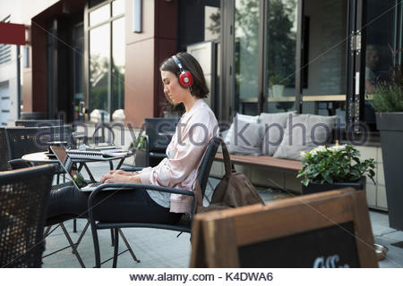 Brunette woman with headphones listening to music and using laptop at sidewalk cafe - Stock Photo
