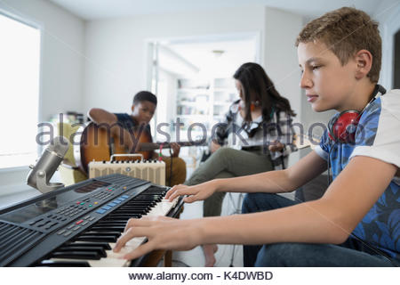 Teenage boy playing keyboard piano, recording music with friends - Stock Photo