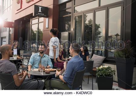 Men friends drinking beer at sidewalk cafe - Stock Photo