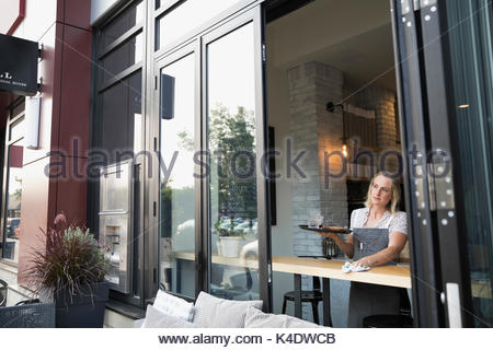 Pensive waitress wiping counter at cafe window - Stock Photo
