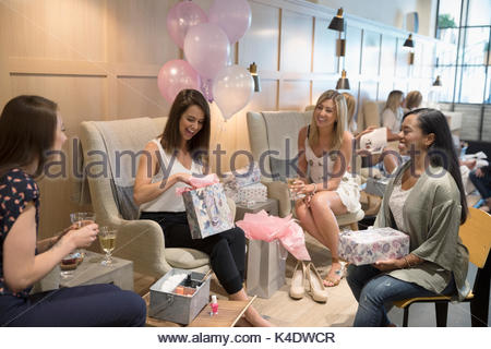 Bride-to-be and bridesmaid friends opening gifts at bridal shower in nail salon - Stock Photo
