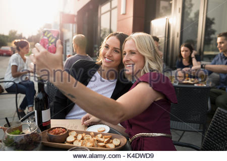 Smiling women friends taking selfie with smart phone, drinking wine and eating appetizers at sidewalk cafe - Stock Photo