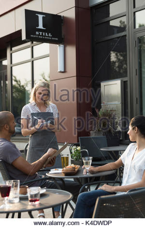 Waitress taking order from couple at table at sidewalk cafe - Stock Photo