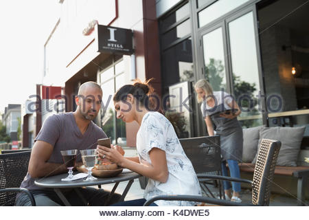 Couple drinking wine and using cell phone at sidewalk cafe - Stock Photo