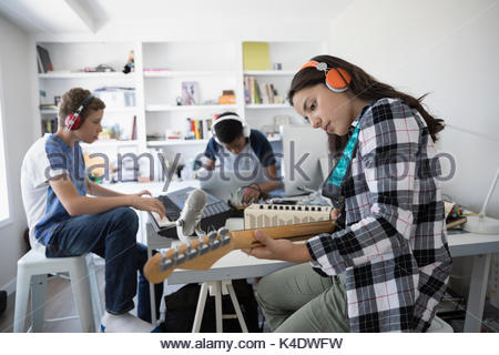 Teenage girl with headphones playing electric guitar, recording music with friends in home office - Stock Photo