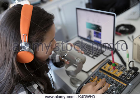 Teenage girl with headphones singing, recording music at microphone equipment - Stock Photo