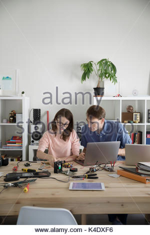 Father and teenage daughter assembling electronics at laptop at dining table - Stock Photo