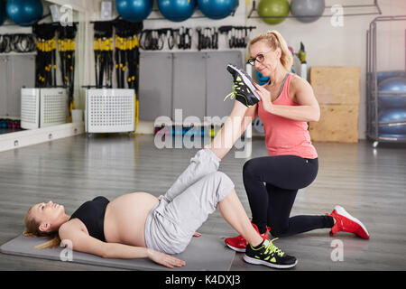 Side portrait of pregnant woman lying on mat exercising with personal trainer - Stock Photo