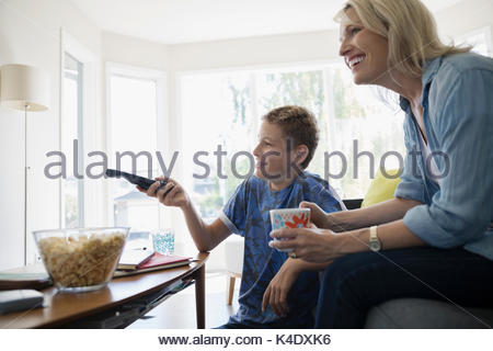 Mother and pre-adolescent son watching TV and eating popcorn in living room - Stock Photo