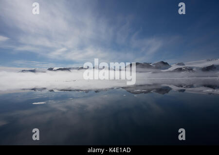 The north coast of Spitsbergen, Svalbard reflected in the calm waters of the Arctic Ocean, with a band of fog forming - Stock Photo