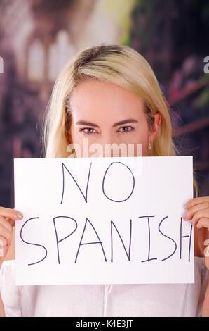 Young mad american blonde woman holding a piece of paper with a description of no spanish, racism, violence or discrimination - Stock Photo