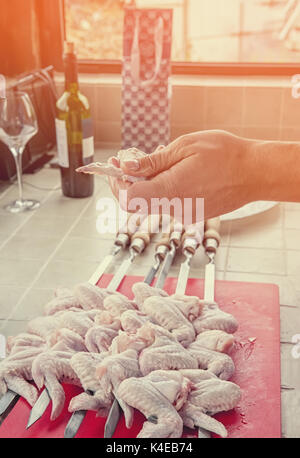 A hand puts pieces of marinated chicken on a spit in the kitchen on a Sunny day. - Stock Photo