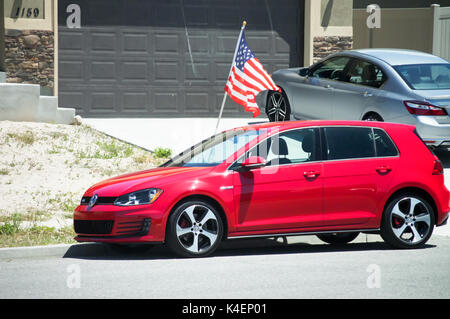 A red golf volkswagon parked beside a united states flag. - Stock Photo