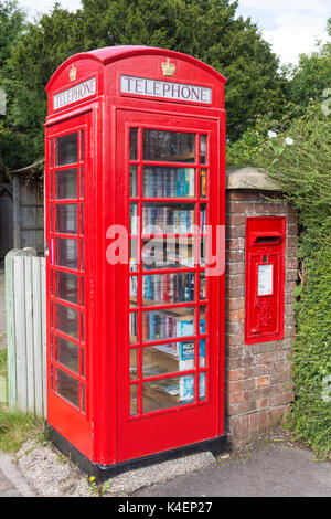 Red telephone kiosk (book exchange) and post box, Chapel Row Stores, Chapel Row, Bucklebury, Berkshire, England, - Stock Photo