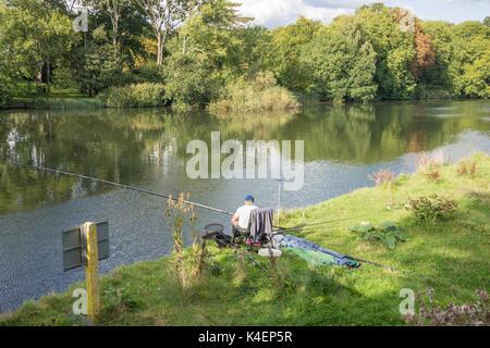 Amateur angler fishing on banks of River Thames, Pangbourne, Berkshire, England, United Kingdom - Stock Photo