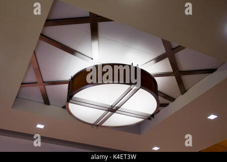 A circular modern light fixture in the ceiling. - Stock Photo