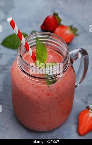 Strawberry smoothies with banana and orange juice in a glass jar, closeup - Stock Photo