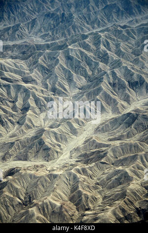 Eroded hills and dry river beds in the desert south of Ica, Peru, South America - aerial - Stock Photo