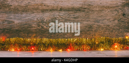 old wooden background with gold tinsel and garland with space for text. the concept of new year Christmas. tinted - Stock Photo