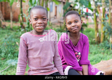 Two nice young girls smiling and sitting on a fallen tree trunk. - Stock Photo