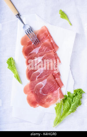 Jamon, spanish ham. Slices of prosciutto crudo with salad leaves on white. Top view. - Stock Photo