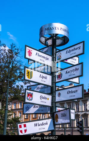 Information signpost showing distances and directions to different  cities - Krakow, Poland. - Stock Photo