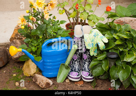 Gardening Tools. Blue Watering Can, Rubber Boots, Gloves And Shovel In Garden. - Stock Photo